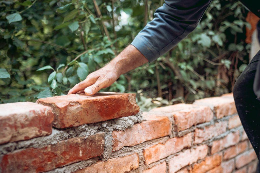 mason worker building with bricks, mortar, trowel. Industrial construction site details.